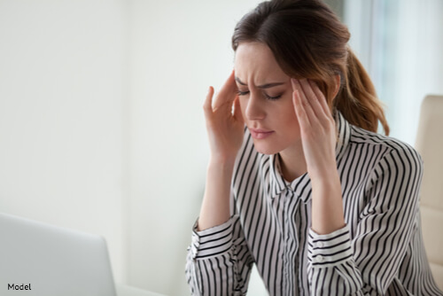Woman with hands on head stressed out