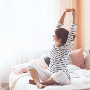 Person stretching in bed