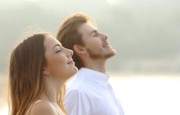 Man & woman taking deep breaths of fresh air